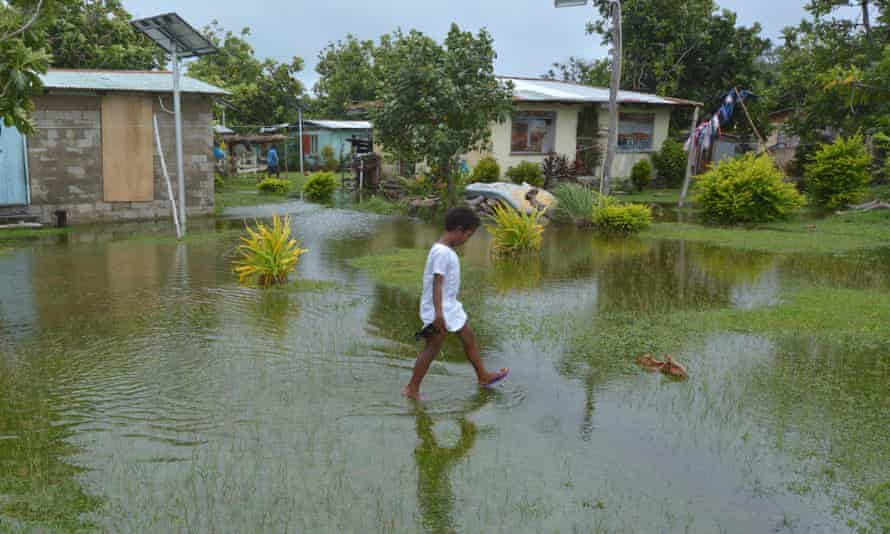 Fijian girl walks over flooded land in Fiji