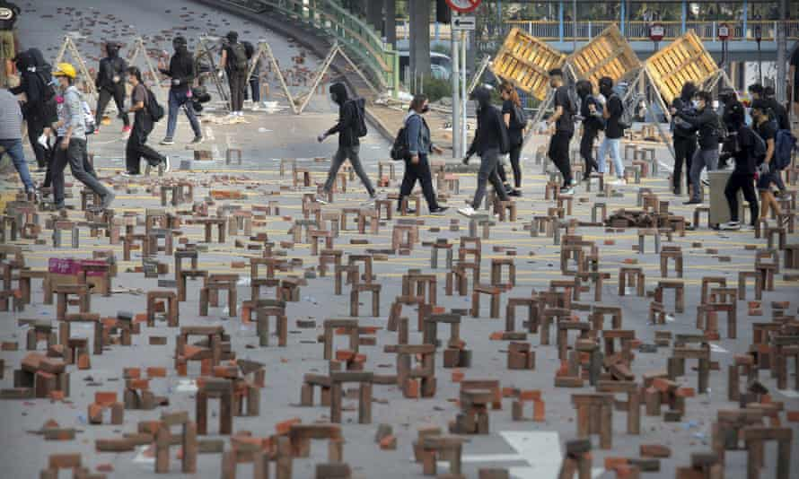 Protesters walk past barricades of bricks on a road near the Hong Kong Polytechnic University