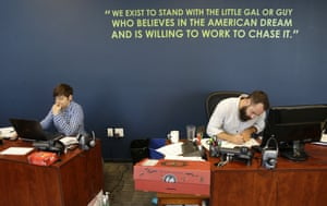 April Gracz, left, and Pano Giannakopoulos, right, Gravity Payments workers next to a wall displaying a company mission statement.