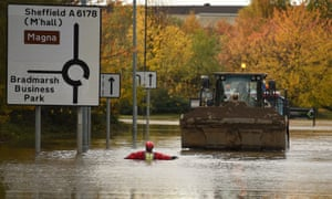 A member of the fire and rescue service wades through flood water as he escorts a JCB towing an truck along a flooded road Rotherham