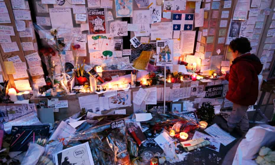 young boy lights candle amid lots of messages and flowers on the ground and on the wall