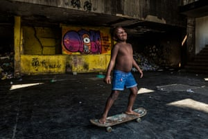 A child rides her skateboard in the abandoned IBGE building in Mangueira