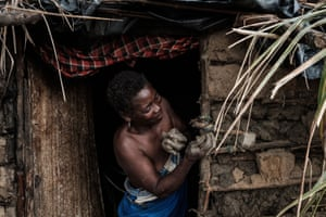 Joana Joni Amelico repairs the mud walls of her house in Beira