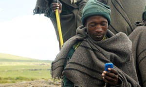 A Lesothan shepherd uses a mobile phone in Northern Drakensberg.