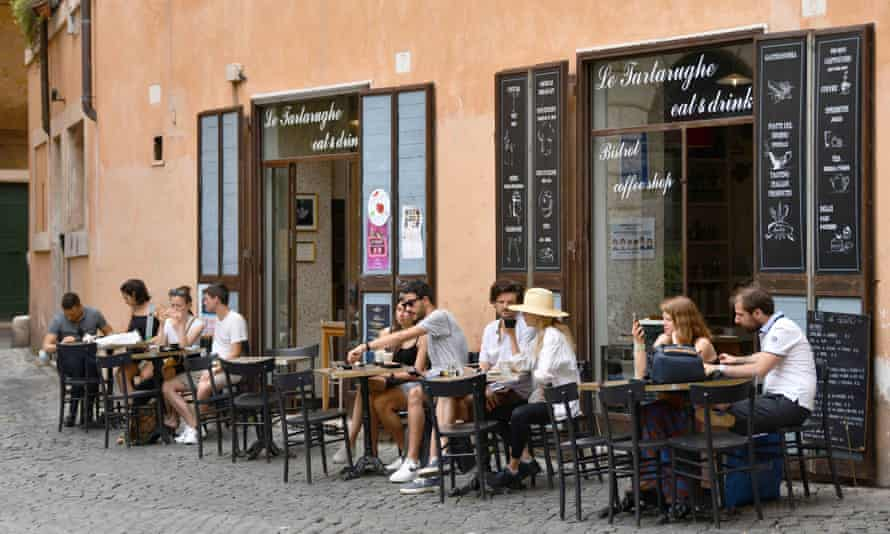 People sit outside a coffee shop in Rome