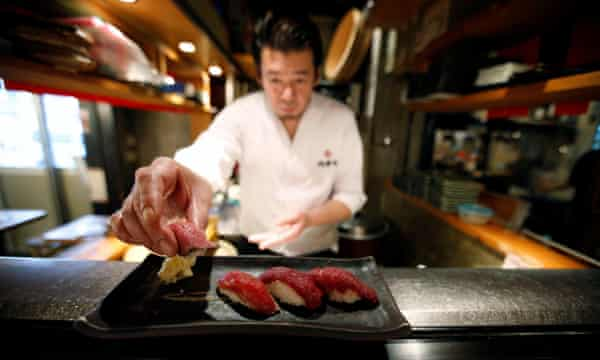A chef prepares a plate at a Nikuzushi (meat sushi) restaurant in Tokyo, including horse (left and second left), duck and beef.