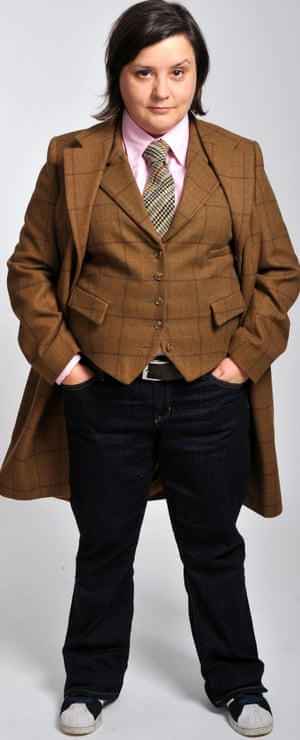 Susan Calman dressed in a shirt and tie, with a matching waistcoat and long coat.