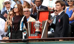 The ladies singles trophy is shown to the crowed inside Court Suzanne Lenglen prior to the ladies singles final .