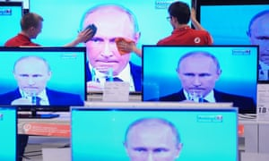 Vladimir Putin is seen on multiple television screens.