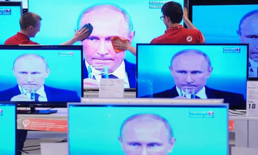 Vladimir Putin is seen on multiple television screens.