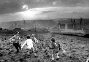 Boys playing football on a hill above Oldham, 1982.