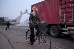 A woman cycles before the Arch of Reunification on the outskirts of the city