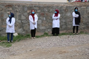 Health workers wait outside while the hospital where they work is disinfected, in Herat, the Afghan city worst affected by the coronavirus outbreak