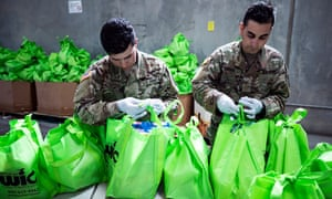 Members of the national guard put food in bags to be delivered to people in need at the Find food bank in Indio, California, on 24 March.