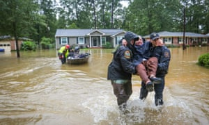 DNR officer Brett Irvin and Lexington County deputy Dan Rusinyak carry June Loch to dry land after she was rescued from her home in Columbia, South Carolina.
