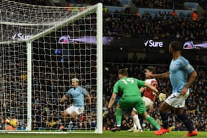 Manchester City's English midfielder Raheem Sterling (R) watches as Sergio Aguero taps home his cross