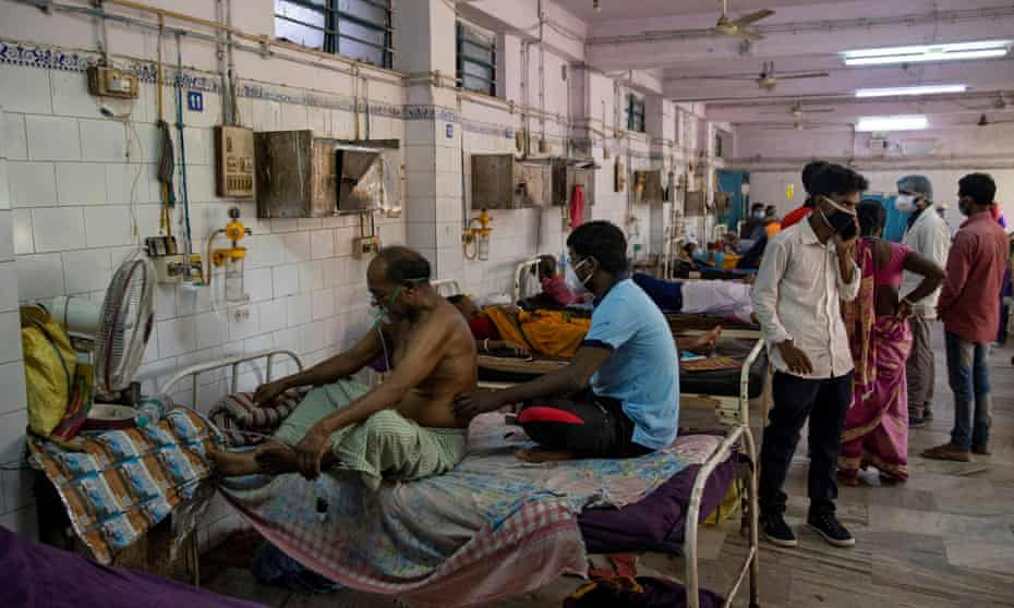 Patients sit on hospital beds inside the emergency ward in India's eastern Bihar state, where 90% of people live in villages.