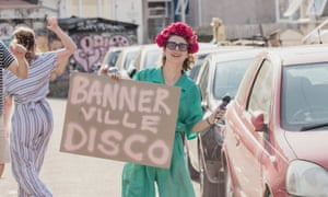 Jesse Meadows in Banner Road, Bristol, with a flower garland in her hair and holding a sign saying Banner Ville Disco