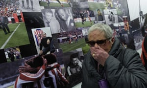 A woman cries next to tributes to Quini outside Sporting Gijón's El Molinón Stadium in Gijón, where Quini died on Tuesday.