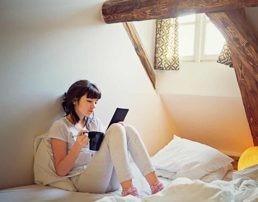A teenage girl reading an e-book in a corner