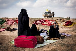 Women and children seen sitting on blankets with their few belongings at a civilian screening point