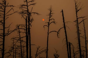 Sunlight filters through smoke from burning forests near the village of Magaras in Sakha