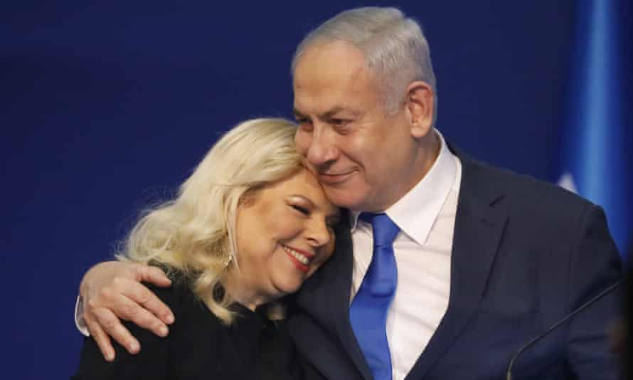 Israeli Prime Minister Benjamin Netanyahu hugs his wife Sara after first exit poll results for the Israeli elections at his party's headquarters in Tel Aviv, Israel, Monday, March. 2, 2020
