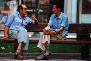 two men chat on a bench