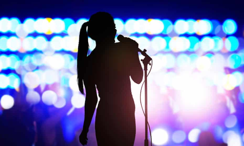 Silhouette of woman with microphone on a stage