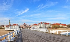 View from the wooden pier, on a sunny day, at Sopot in northern Poland. In the background are grand town buildings with red-tiled roofs.