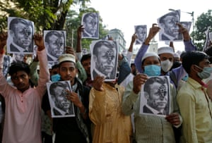 Kolkata, India. Supporters of the All Bengal Minority Youth Federation display defaced portraits of the French president, Emmanuel Macron, during a protest against the publication in France of cartoons depicting the prophet Muhammad