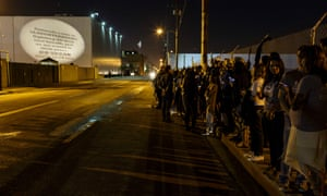 """A """"vegan batman light"""" is projected onto the wall of Farmer John while a security guard peeks over the wall to observe the activists, who usually stay for three to four hours."""