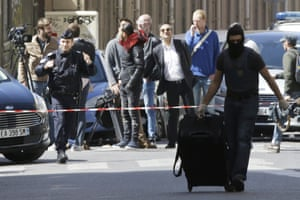 A masked police officer pulls a suitcase after searches in Marseille. Security has been a major campaigning issue in the presidential election.