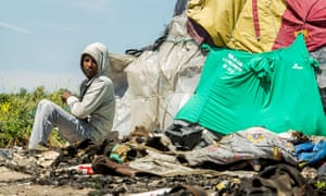 """A migrant stands next to his tent in the """"New Jungle"""" in Calais, France."""