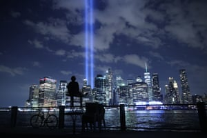 A person watches the Tribute In Light shine into the sky from Lower Manhattan during a test before the 20th anniversary of the September 11 terrorist attacks.