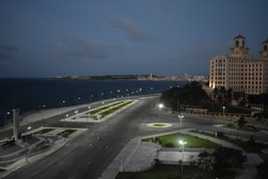 A police officer patrols a beach road in Havana. For the first time since March, a curfew has been imposed in the capital, requiring residents to stay off the streets from 7pm to 5am
