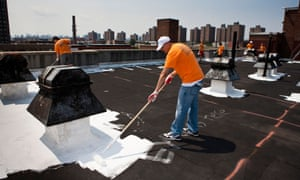 Volunteers paint a New York rooftop with specialised coating material that has a high solar reflectivity.