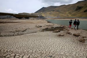 Motorcyclists stand on the dried Ajuan Khota dam, a water reserve affected by drought near La Paz