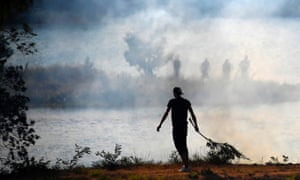 A man tries to extinguish a fire in Bormes-les-Mimosas. At least 10,000 people, including thousands of holidaymakers, were evacuated after wildfires broke out in southern France.