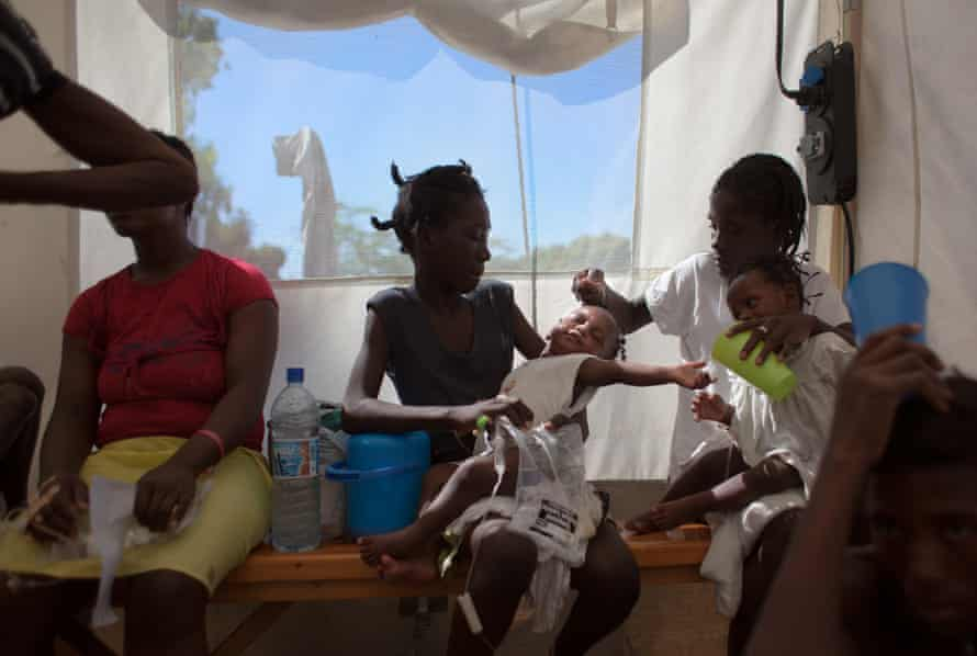 A pair of twins with cholera are held by their mother, right, and sister, centre, as they receive IV drips at a cholera clinic in Port-au-Prince