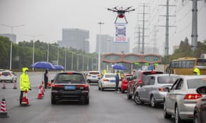 A drone carrying a QR code placard near a toll station in Shenzhen to register vehicles returning to the city.