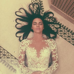 Kendall Jenner lying on the ground in a white lace dress