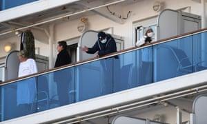 Passengers stand on balconies on the Diamond Princess cruise ship on Monday.