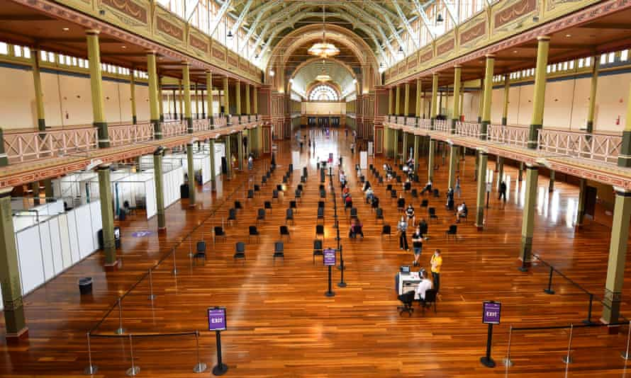 people seated in a vast victorian hall in Melbourne waiting to get covid vaccination