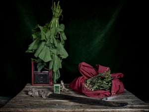 A table in Natalie Wato's home in Bossembélé with a machete, radio, chicken foot talisman, box of matches, squash leaves and bag of ground nuts