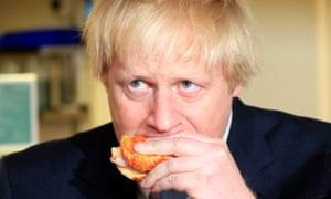 Boris Johnson eating a bacon sandwich.