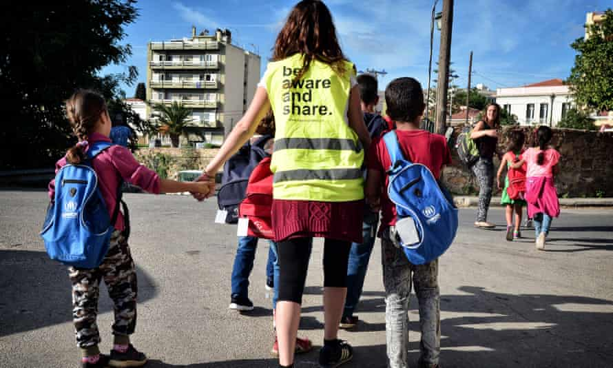Volunteers walk a group of refugee children towards their school on the island of Chios.