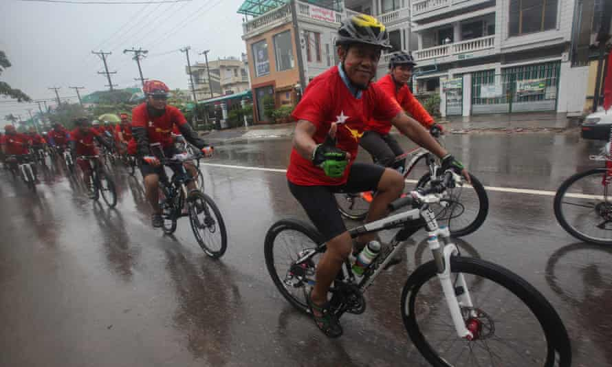 Supporters of Aung San Suu Kyi promote the NLD party as monsoon rains continue.