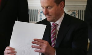 Enda Kenny holds the order dissolving the Irish parliament