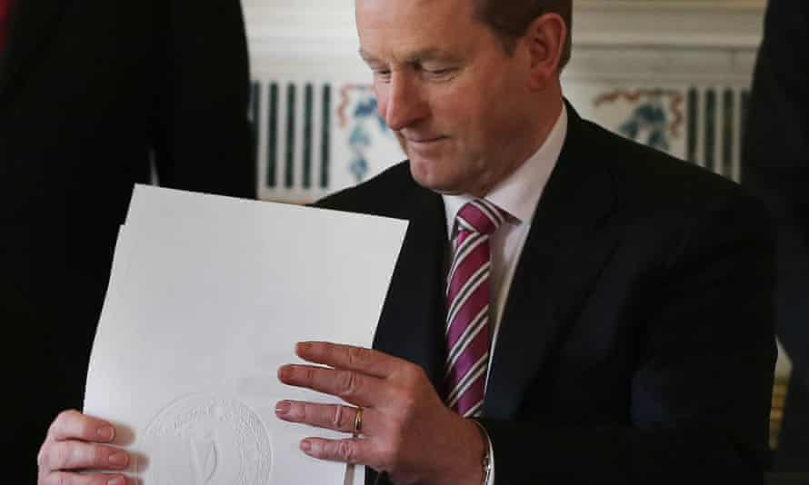 Enda Kenny holds the order dissolving the Irish parliament